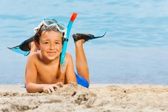 Little boy in scuba mask and flippers on the beach. Little boy laying on the sea beach in flippers and scuba mask enjoying summer vacation royalty free stock photos