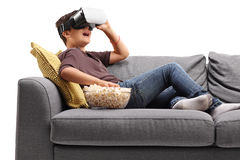 Little boy laying on sofa using VR goggles and eating popcorn Royalty Free Stock Photo