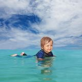 Little boy laying in the water. Wearing a wet suit Stock Images