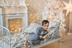 Little boy lays on a bed in a room with Christmas tree. A little boy lays on a bed in a room with Christmas tree and a fireplace Royalty Free Stock Image