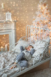 Little boy lays in a room with Christmas tree. A little boy lays on a bed in a room with Christmas tree and a fireplace Royalty Free Stock Images