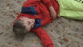 Little crying boy lays on sand. Little boy lays on sand and cries. Sad adorable boy is naughty. The boy disappointed from something stock video