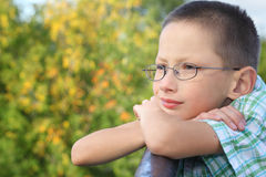 Little boy is lean elbow on bridge fence. And looking forward Stock Photos