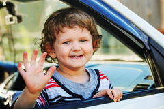 Little boy leaned out the window of a car and waving his hand. Stock Photo