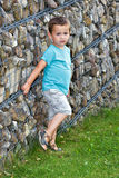 Little boy leaning against the stone fence Royalty Free Stock Photography