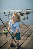 Little boy learn to catch fish in lake or river. Fishing, angling, activity, adventure, sport. Childhood, education, training. Child with fishing rod on wooden royalty free stock images