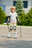 Little Boy learning rollerblading. Little boy learning to roller skate and wearing protection elbow and knee pads Stock Photos