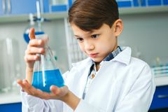Little child with learning class in school laboratory observation. Little boy learning in school laboratory holding bulb close-up observing changes in a blue stock photos
