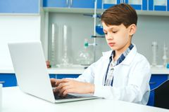 Little child with learning class in school laboratory typing on laptop stock image
