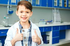 Little child with learning class in school laboratory thumbs up royalty free stock image