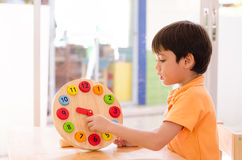 Little Boy Learning Time With Clock Toy Of Montessori Educationa Stock Photos
