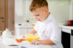 Little boy learning to bake reading the recipe Royalty Free Stock Images