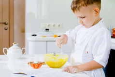Little boy learning to bake reading the recipe Stock Image