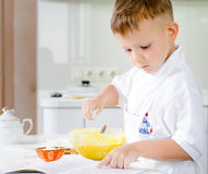 Little boy learning to bake reading the recipe Stock Images