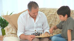 Little boy learning to play chess stock footage