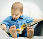 Little boy is learning to read. Portrait of a little boy with a book in his hands Stock Photo