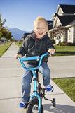 Little boy learning to ride a bike with training wheels Royalty Free Stock Image