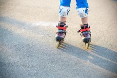 Little boy learning to roller skate in summer park. Children wearing protection pads for safe roller skating ride. Active outdoor royalty free stock photography