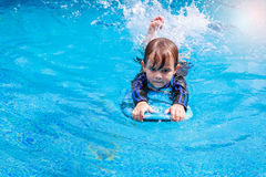 Little boy learning to swim in pool, practicing with foam pad Royalty Free Stock Photography