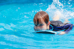 Little boy learning to swim in pool, practicing with foam pad Stock Image