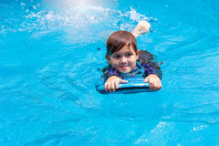Little boy learning to swim in pool, practicing with foam pad Royalty Free Stock Photo