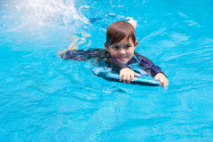 Little boy learning to swim in pool, practicing with foam pad Stock Images