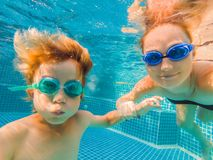Little boy learning to swim in a swimming pool, mother holding the child.  royalty free stock image