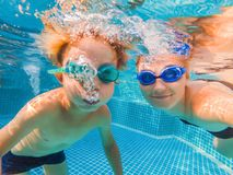 Little boy learning to swim in a swimming pool, mother holding the child.  stock photos