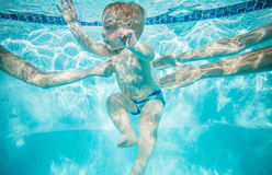 Little boy learning to swim underwater. Mother and female instructor holding child Stock Photos