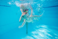 Little boy learning to swim underwater in pool. Mother or instructor holding child Stock Photography