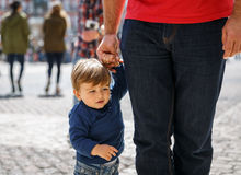A little boy learning to walk from the hand of an adult Royalty Free Stock Photos
