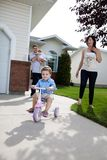 Little Boy Learning Tricycle. Little boy learning to ride tricycle while parents watch stock photography