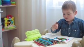Little boy learns to draw with colored pencils stock video