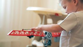 A little boy learns to lift and lower the load on the crane stock footage