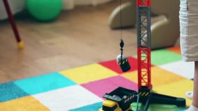 A little boy learns to lift and lower the load on the crane HD stock footage