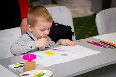 A little boy learns to paint with a brush stock images