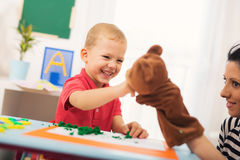 Little boy during lesson with his speech therapist. Learning through fun and play stock images