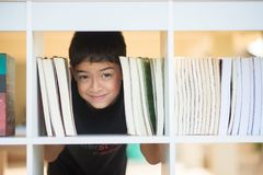 Little boy in the library at school face between books stock photography