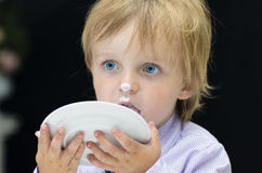 Little Boy Licking his Plate. On black background Royalty Free Stock Photos