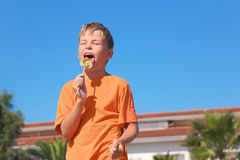 Little boy licking multicolored lollipop Royalty Free Stock Photo