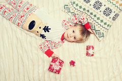 Little boy lie on the bed. With gift in pajamas Royalty Free Stock Photo