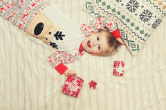 Little boy lie on the bed with gift. In pajamas Royalty Free Stock Photos