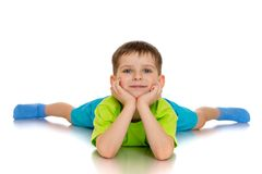 Little boy lies on the floor with their legs wide. A little boy lies on the floor with their legs wide open - isolated on white background Royalty Free Stock Image