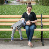 Little boy lies on his mother`s lap sitting on the bench. Happy little boy lies on his mother`s lap sitting on the bench in green park Stock Image