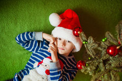 Little boy is lies near fir-tree. New Year's holidays.  in a striped T-shirt with Santa Claus Stock Images