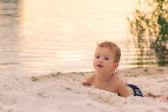 Little boy Lies on the river sand bank at sunset Royalty Free Stock Photos