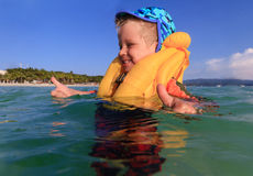 Little boy in life jacket playing with water on the beach Royalty Free Stock Photography