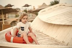 Little boy with lifebuoy on tropical beach. Child sit in ring buoy on sunny day. Kid with blond hair have fun outdoor royalty free stock photos