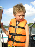 Little Boy In Lifejacket. Cute little boy in a bright orange lifejacket on a boat in the Missouri Ozarks Stock Image