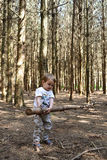 Little boy lifting tree in woodland. Little boy lifting long tree trunk on his own in the woods Stock Photography